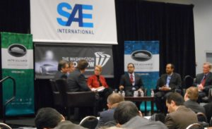 SAE Plenary Panel as seated from the left end of the group: Joseph B. White, Reuters' Transportation Editor;  John Bozzella, President & CEO, Global Automakers; John DeCicco, Research Professor, Energy Institute at the University of Michigan; Anne Ferro, President & CEO, American Association of Motor Vehicle Administrators; Reuben Sarkar, Deputy Assistant Secretary for Transportation, U.S. Department of Energy; Ravi Shanker, Executive Director, Morgan Stanley Research; Dan Smith, Senior Associate Administrator for Vehicle Safety, National Highway and Transportation Safety Administration